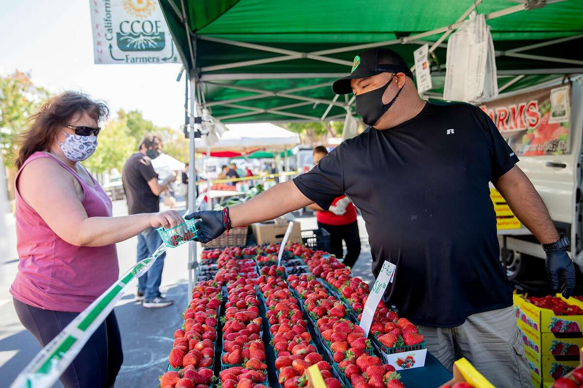 Chay's Farm vendors wear masks while serving customers at the Benicia Farmer's Market in Benicia, Calif. Thursday, July 30, 2020. Alameda, San Mateo and Solano counties were downgraded from the highest-risk purple category to red status Tuesday morning.