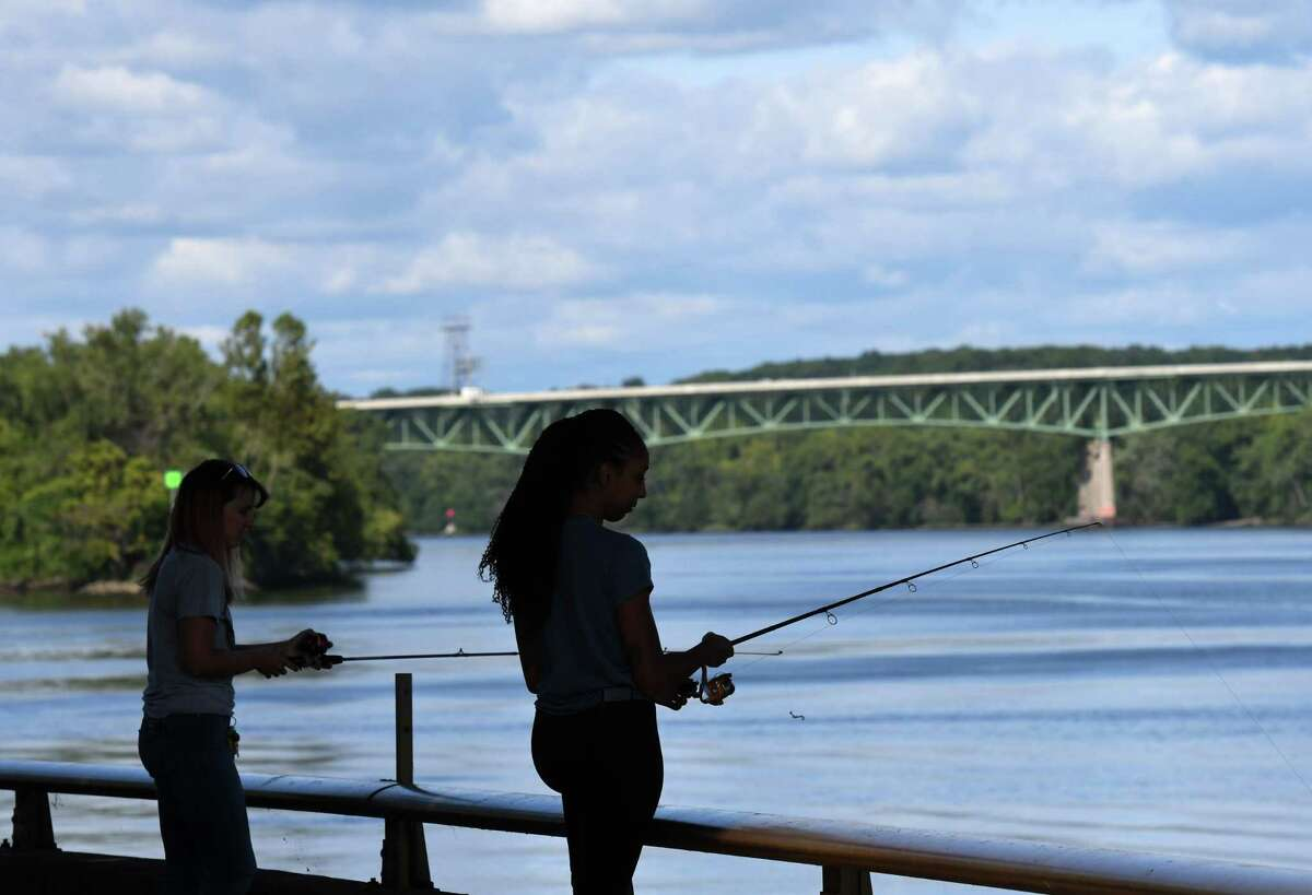Shelby Taylor, left, and Angie Gomez, right, of Albany fish the Hudson River under Livingston Avenue Bridge on Friday, Aug. 28, 2020, at Corning Preserve in Albany, N.Y. (Will Waldron/Times Union)