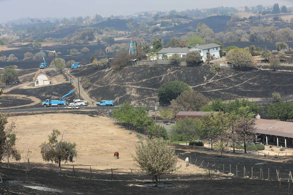 From a view where Larry Woodruff's home once stood on Scenic Ranch Lane, PG&E crews can be seen working in the area in Vacaville, Calif., on Wednesday, August 25, 2020.