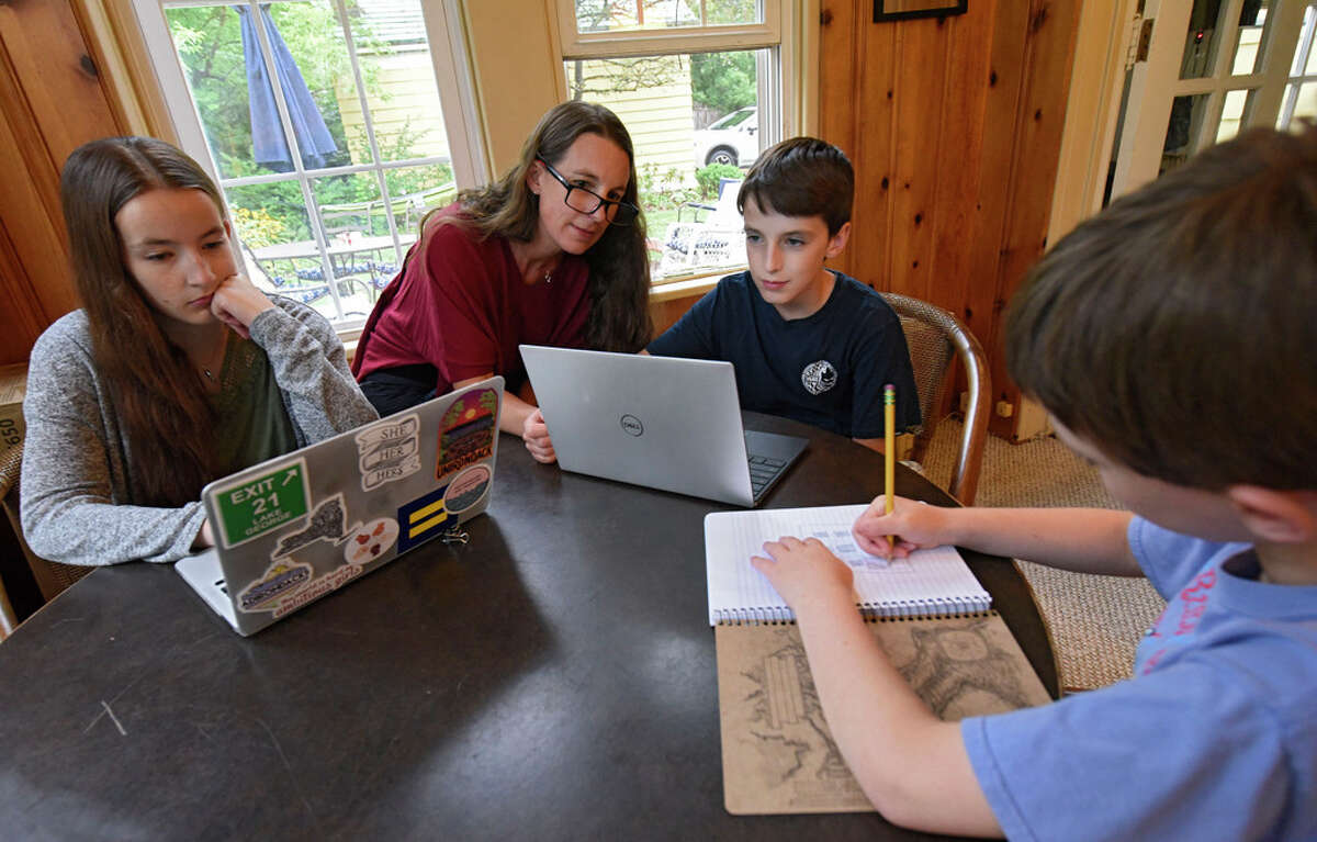 Erin Tobin, second from left, helps her children Sarah Bearden, left, Myles Bearden, second from right, and Eli Bearden prepare for the school year in their home on Thursday, Aug. 27, 2020 in Albany, N.Y. (Lori Van Buren/Times Union)