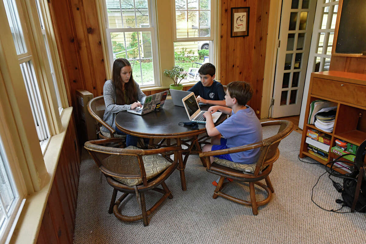 From left, Sarah Bearden, and her brothers Myles Bearden and Eli Bearden are seen on their computers in their home on Thursday, Aug. 27, 2020 in Albany, N.Y. (Lori Van Buren/Times Union)