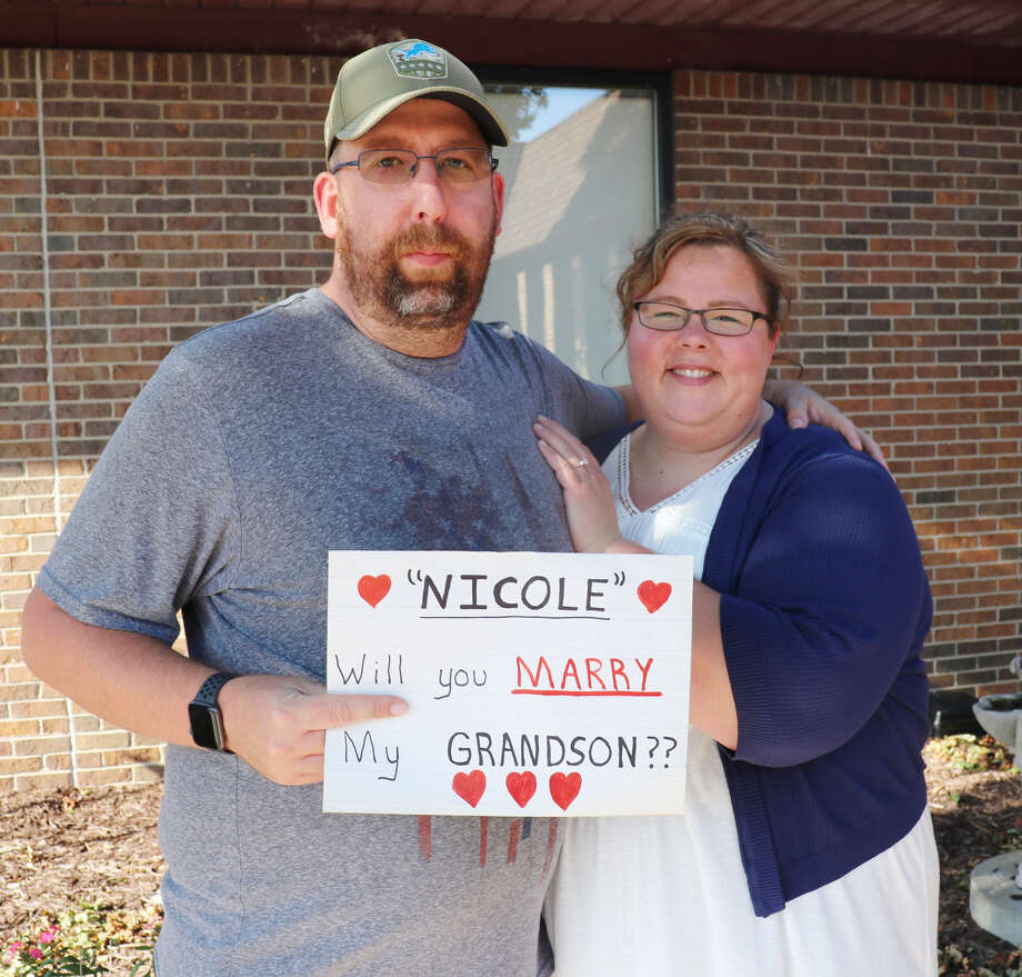 Newly engaged couple Josh Chupp and Nicole Curnett pose with the sign held up by Chupp's grandmother during their marriage proposal.Chupp asked his grandmother to be a part of the proposal after realizing COVID-19 restrictions would prevent her from attending their wedding. Photo: Photo Courtesy Of Spectrum Health