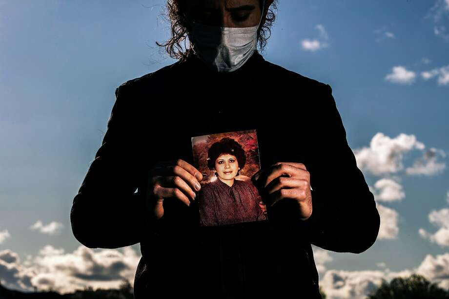 Amir holds a photo of his mother, Azar Ahrabi of Santa Clara County, who was among the first to die of COVID-19 in the Bay Area. Photo: Stephen Lam / Special To The Chronicle