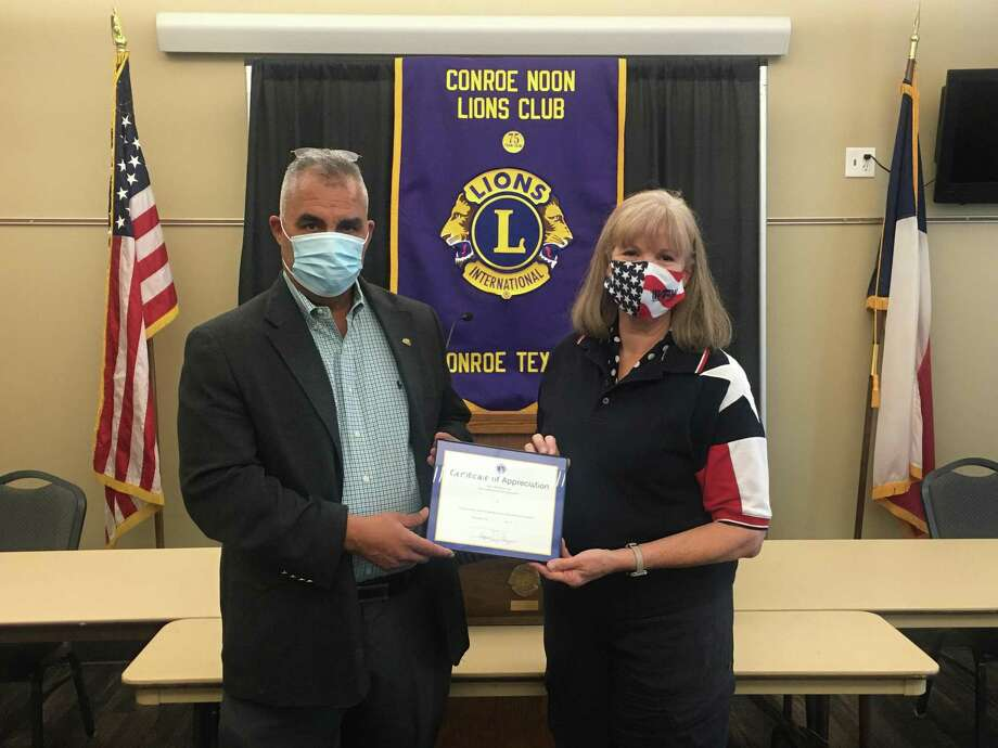 Conroe Noon Lions Club President, Rafael Perez, left, congratulates Lion Connie McNabb, right, the club's Lion of the Month for July, for her photography efforts at the blood drive, Tacos for Teachers, and our Service Saturday Project. Photo: Courtesy Photo