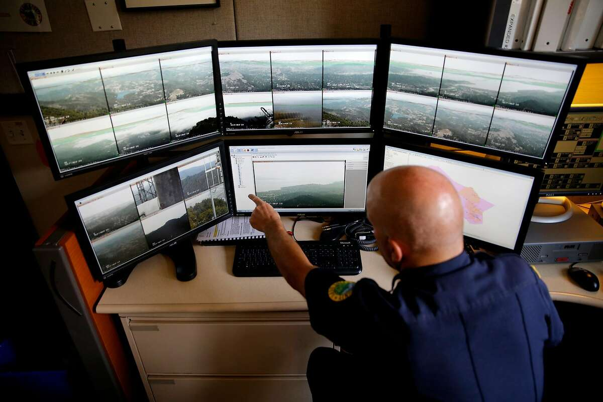 Battalion chief Michael Giannini points out details on screens showing live photos from cameras looking for wildfires while at Marin County Fire Department headquarters in Woodacre, California, on Thursday, Aug. 6, 2015.