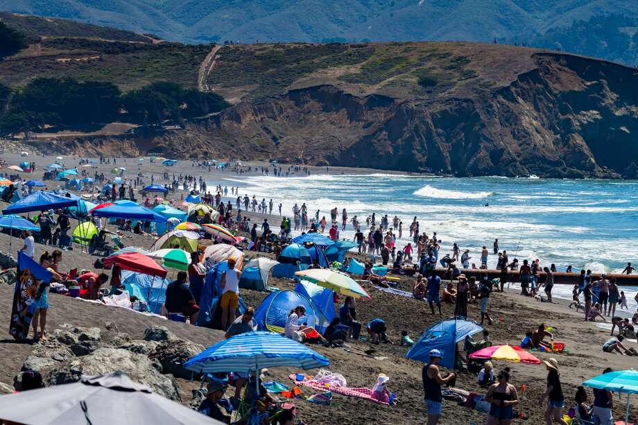 People flock to Sharp Park Beach in Pacifica on Aug. 15, 2020, as temperatures hit 90 degrees. Some think this is too crowded for safety during a pandemic. Pacifica plans to close beaches over the Labor Day weekend. (Photo courtesy of David Chamberlin.) Photo: David Chamberlin/Special To SFGATE