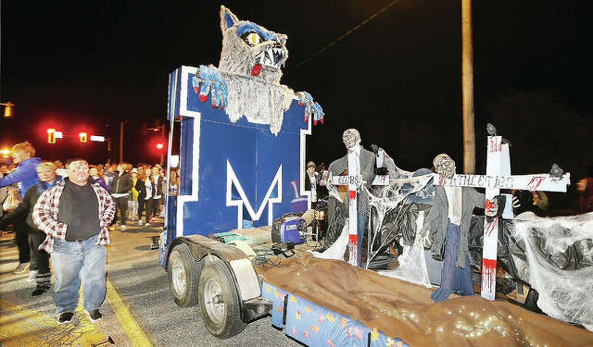 The Marquette Catholic High School float moves down East Broadway in Alton last year during the 103rd Annual Alton Halloween Parade, followed by what looked like most of the student body who handed out candy to the hundreds of children on the route. Parade organizers on Friday announced pandemic concerns have forced the cancellation of this year's parade.