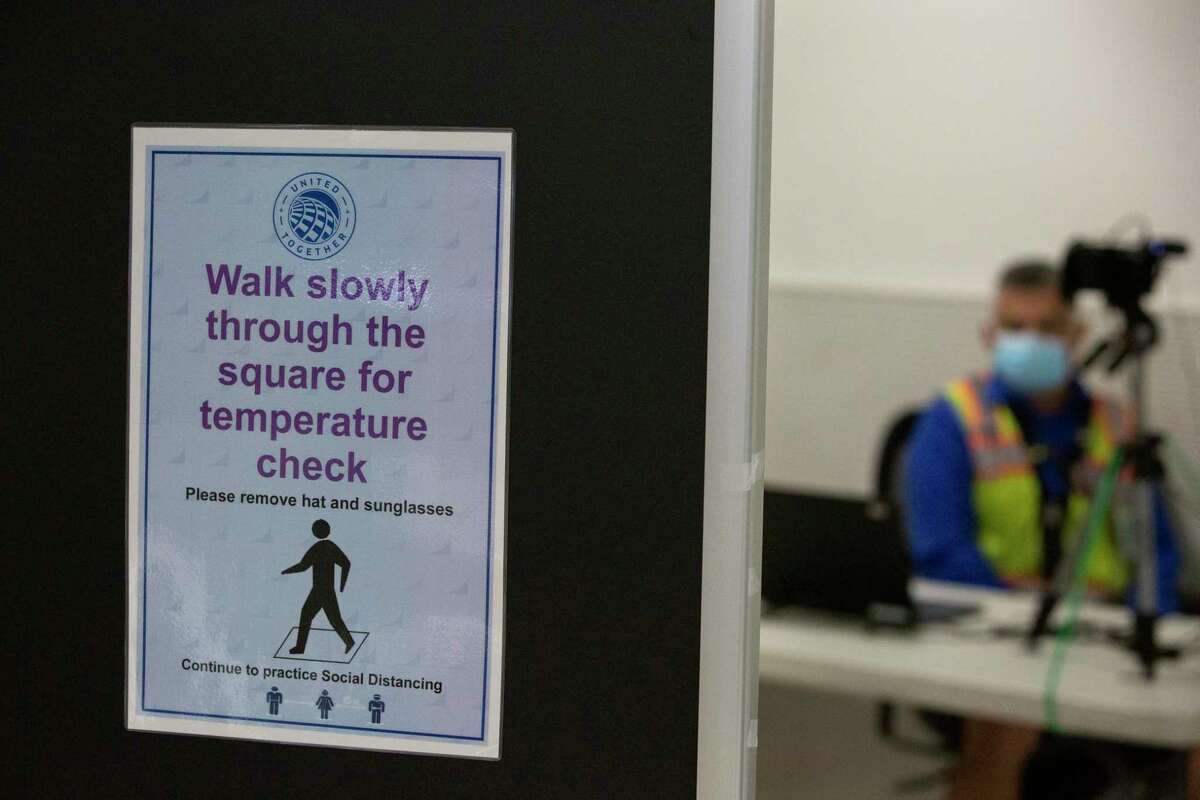 Signs for temperature screening of employees are shown Tuesday, July 7, 2020, at George Bush Intercontinental Airport in Houston. In July, 946,000 passengers traveled through IAH, down 77 percent from 4.2 million during July 2019, according to the Houston Airport System.