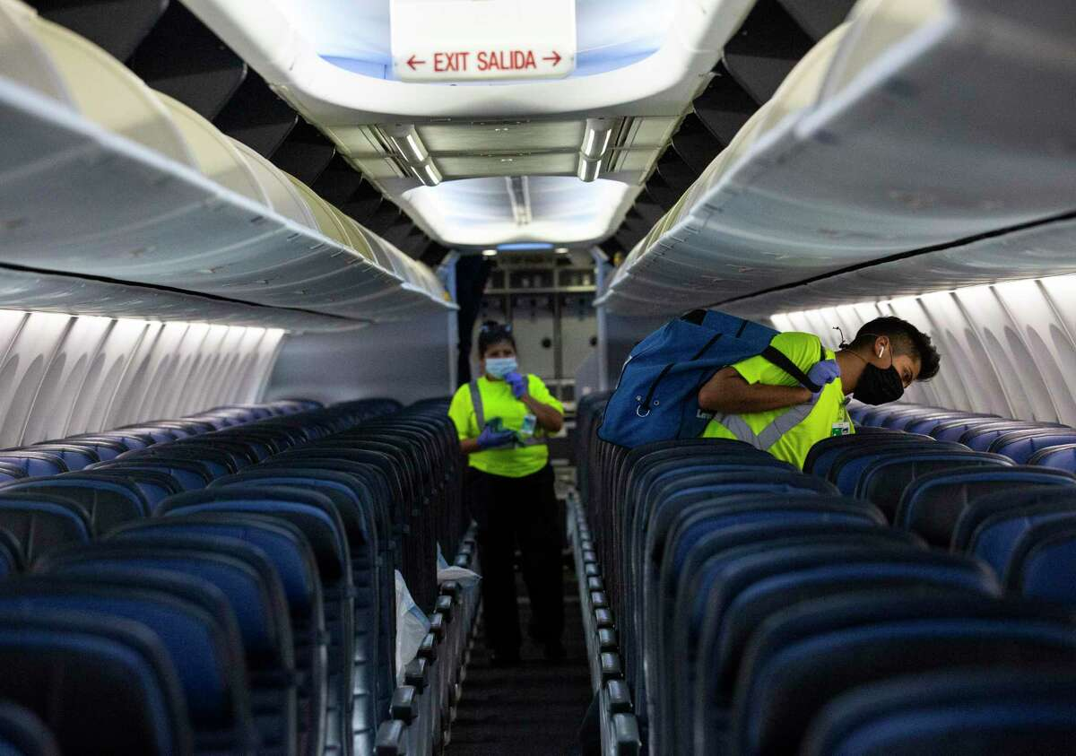 G2 Secure Staff members clean an aircraft before the next flight Tuesday, July 7, 2020, at George Bush Intercontinental Airpo in Houston. In July, 946,000 passengers traveled through IAH, down 77 percent from 4.2 million during July 2019, according to the Houston Airport System.