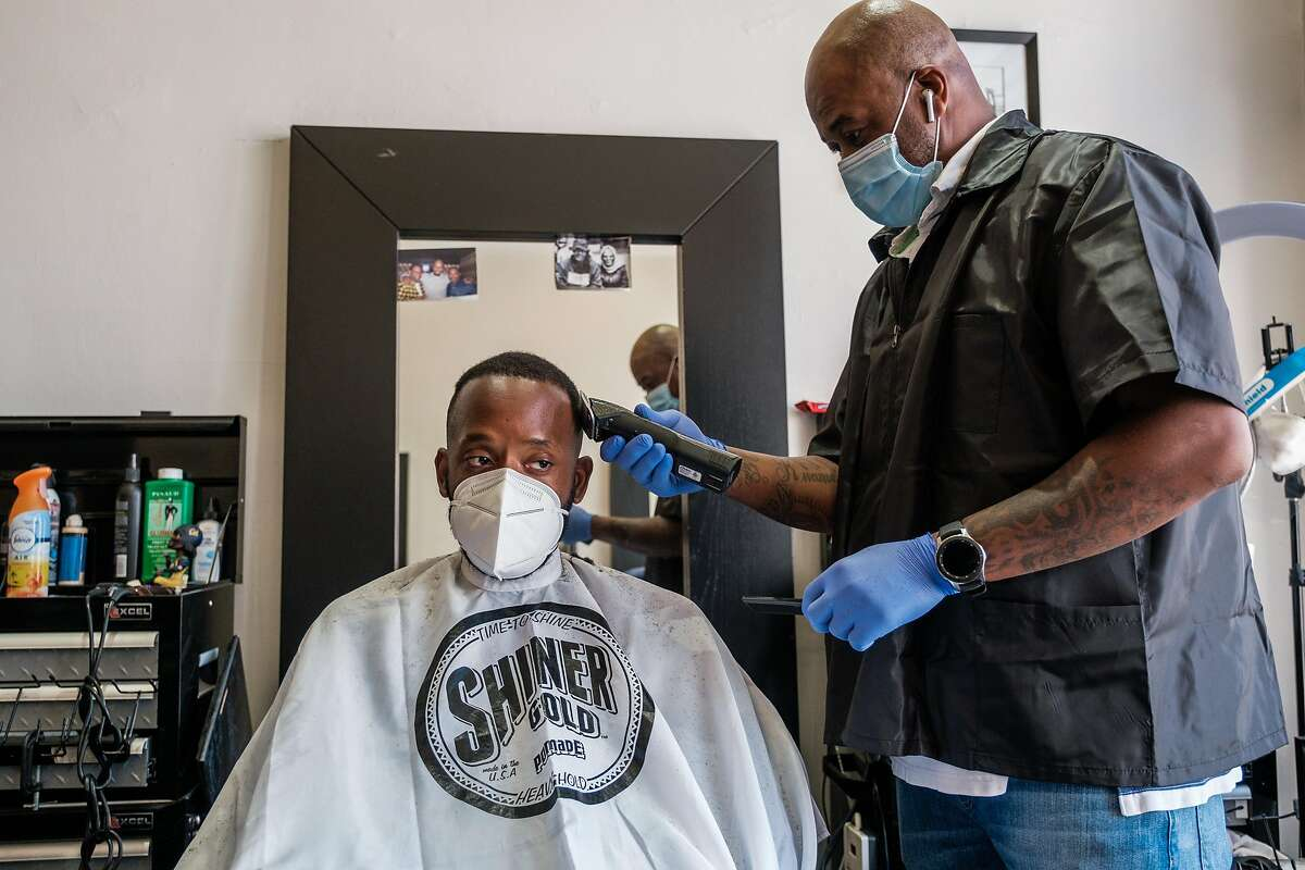 Barber Lennotch Taplett cuts long time customer Brian Hill's hair at Details Barbershop & Grooming Lo in San Francisco on Tuesday, June 30, 2020.