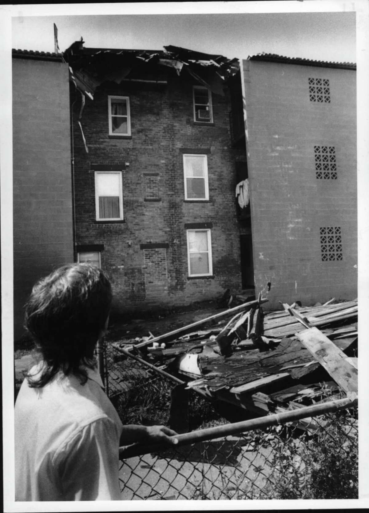 North Mohawk Avenue, Cohoes, New York - Arthur Murray of Cohoes, who lives directly behind the apartment building whose roof was blown off during Tuesday night's storm, looks at the debris on the roof and also in the backyard of the apartment building. August 29, 1990 (Paul D. Kniskern, Sr./Times Union Archive)