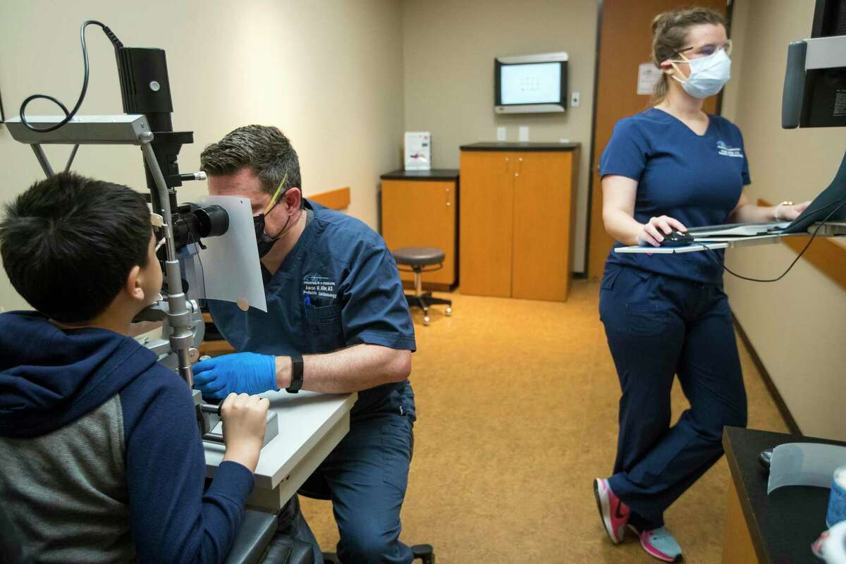 Dr. Aaron M. Miller, center, examines Noah Garcia as orthoptist Angela Dillon takes note at Houston Eye Associates on Thursday, April 9, 2020 in The Woodlands.