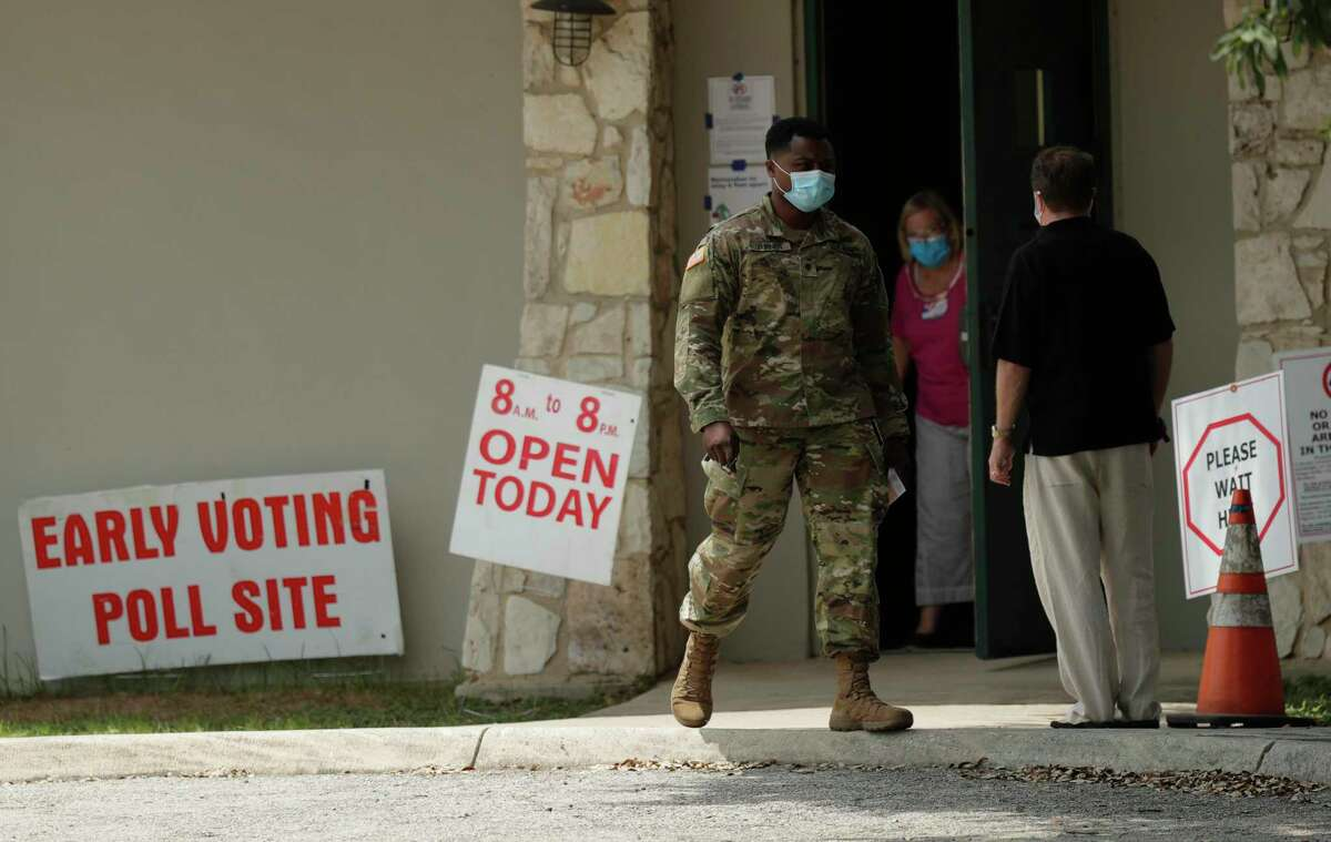 Ellen Ott, center, controls the flow of early voters at a polling site, Tuesday, July 7, 2020, in San Antonio. Polling site workers are wearing masks and taking other precautions due to the COVID-19 outbreak. (AP Photo/Eric Gay)
