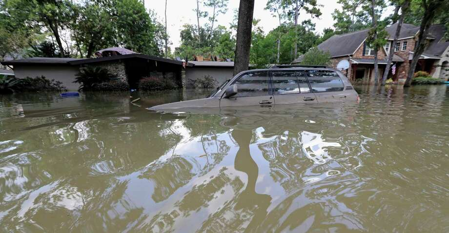 FILE - In this Sept. 4, 2017, file photo, a vehicle is submerged in floodwater in the aftermath of Hurricane Harvey in Houston. Senior U.S. Judge Charles Lettow in Washington. D.C. ruled Tuesday, Dec. 17, 2019, the U.S. Army Corps of Engineers is liable for damages to a group of Houston-area homes and businesses flooded by two federally owned reservoirs during Hurricane Harvey because the inundation was due to how the federal government built and maintained the dams. (AP Photo/David J. Phillip, File) Photo: David J. Phillip, STF / Associated Press / Copyright 2017 The Associated Press. All rights reserved.
