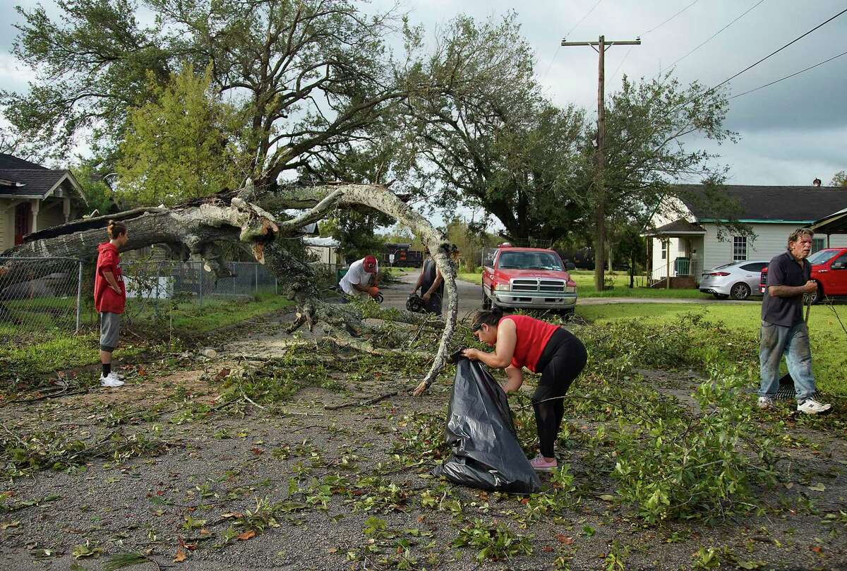 Neighbors clear out a tree that blocks access to their street on 11th and Main in Orange, Texas as recovery efforts continue in Orange following Hurricane Laura on Friday, Aug. 28, 2020.