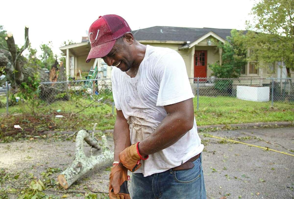 Covered in sweat and sawdust, Justin Johnson laughs as he pauses while using a chainsaw to remove a tree in front of his brother-in-laws house in Orange,Texas following Hurricane Laura on Friday, Aug. 28, 2020.