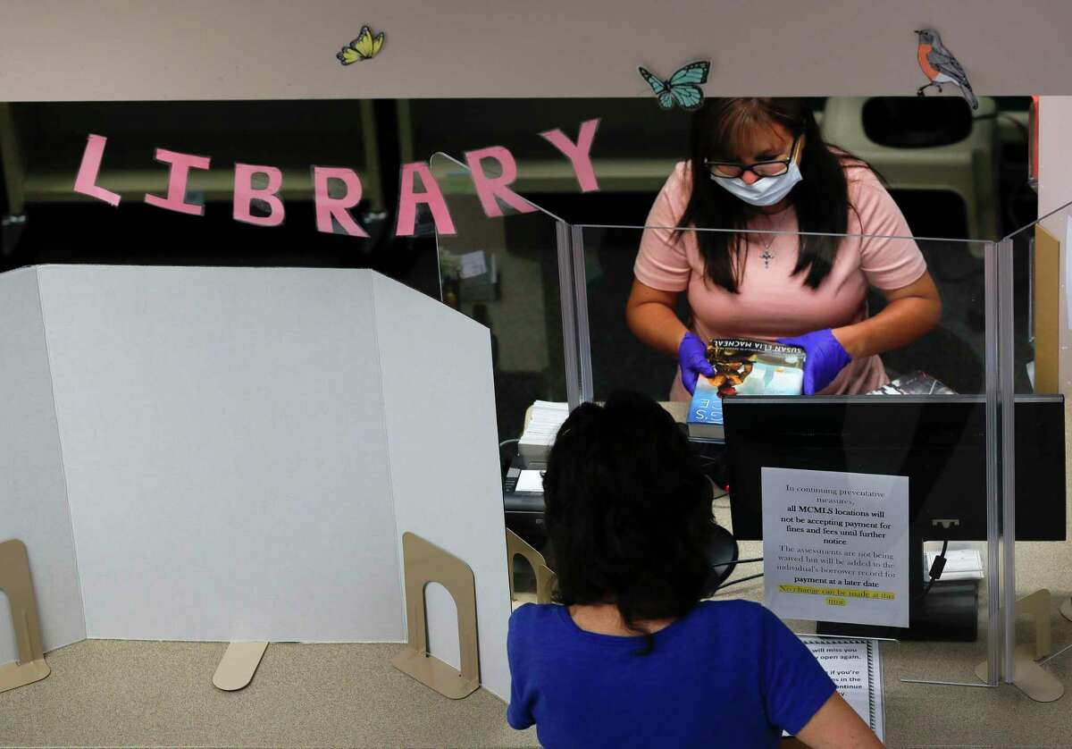 Circulation Coordinator Ruby Chandler scans a book for a visitor in May after the Montgomery County Central Library in Conroe reopened to the public.
