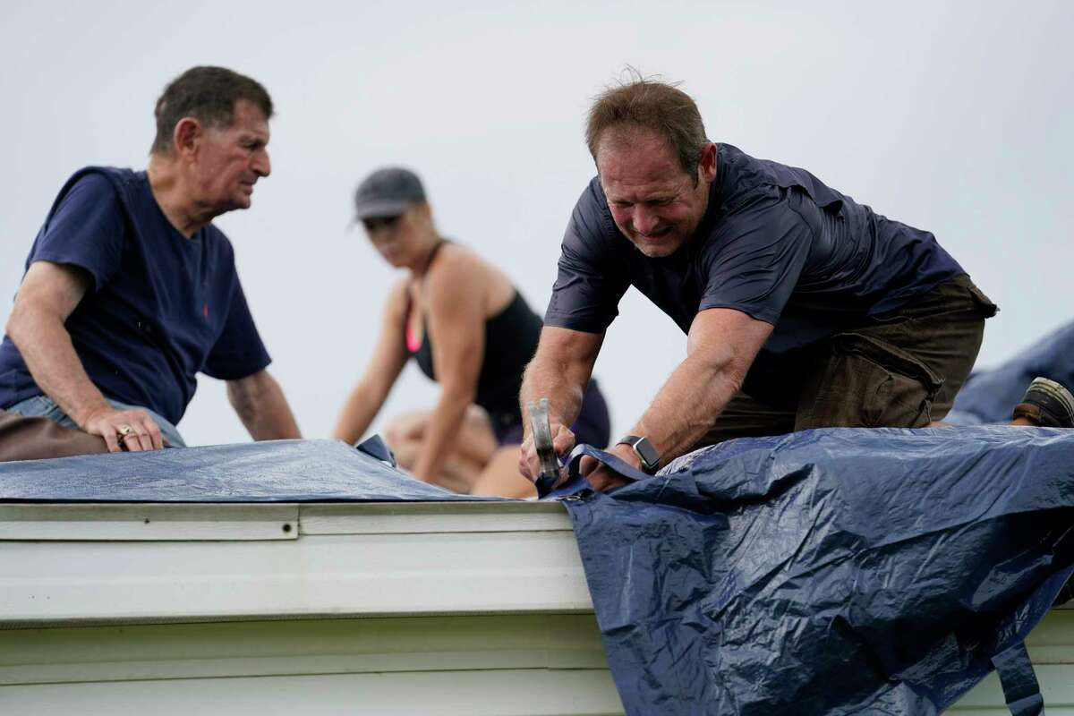 Bob Primeaux, right, works with his son Robbie work a roof that was damaged on Friday, Aug. 28, 2020, in Homewood, La., in the aftermath of Hurricane Laura. (AP Photo/Gerald Herbert)