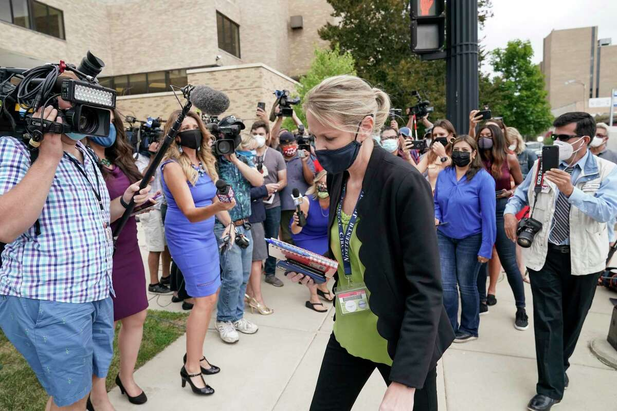 Kasey Morgan, a public information officer for the Lake County Court, walks away from reporters outside the Lake County courthouse following the extradition hearing for Kyle Rittenhouse Friday, Aug. 28, 2020, in Waukegan, Ill. A judge agreed Friday to delay for a month a decision on whether the 17-year-old from Illinois should be returned to Wisconsin to face charges accusing him of fatally shooting two protesters and wounding a third during a night of unrest following the weekend police shooting of Jacob Blake in Kenosha. (AP Photo/Morry Gash)