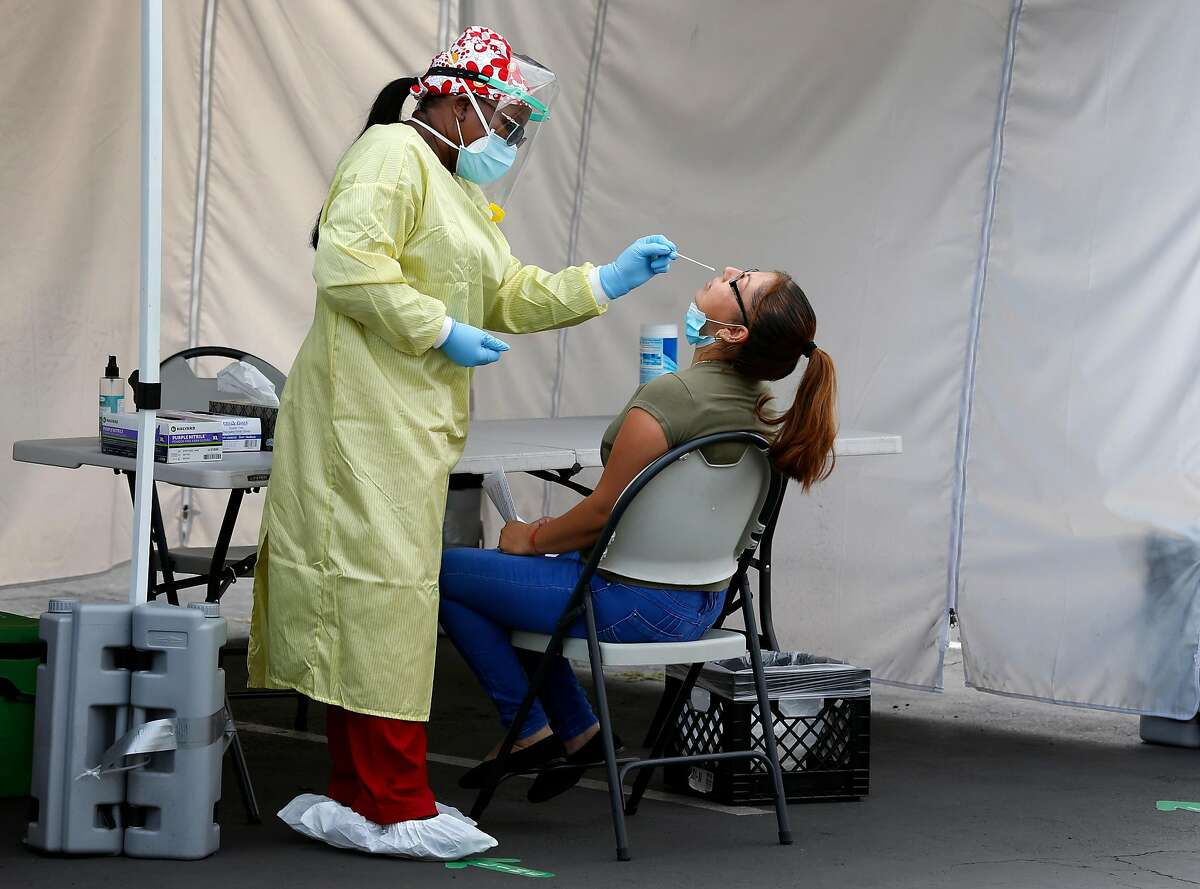 A health care worker administers a nasal swab test to a resident at a walk-up COVID-19 testing site at Roots Community Health Center in Oakland. The Bay Area is seeing a rise in cases.