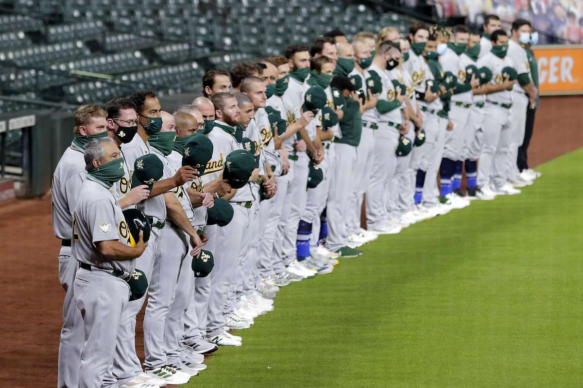 After a moment of silence, Oakland Athletics players wave their hats to the Houston Astros before walking off the field in protest of racial injustice before the start of their baseball game Friday, Aug. 28, 2020, in Houston. (AP Photo/Michael Wyke)