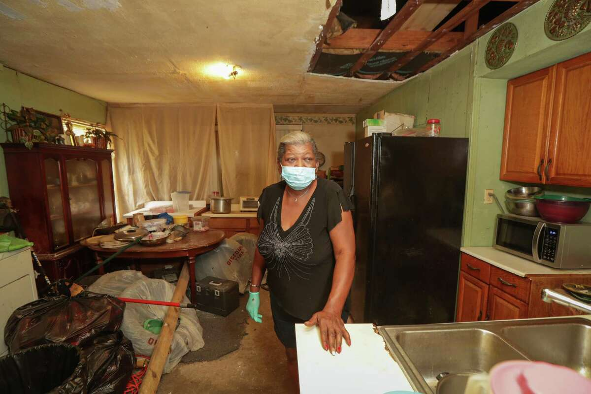 Juanita Hall in the kitchen of her Hurricane Harvey-damaged home Friday, Aug. 28, 2020, in Houston. About four months before Hurricane Harvey, Juanita Hall's mother died of a heart attack, leaving Juanita and her brother with her house. Harvey then brought extensive damage to the home - damage that Hall has been unable to fix through the city's recovery program, which has been plagued by delays.