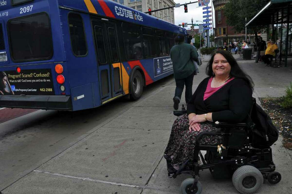 Denise Figueroa, the new chairwoman of the CDTA board, has helped raise CDTA's awareness of issues faced by bus patrons with special needs. She appears in Troy with a CDTA bus. ( Philip Kamrass / Times Union )