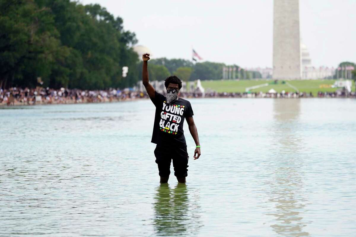 A man stands in the Reflecting Pool as people attend the March on Washington, Friday Aug. 28, 2020, in Washington, on the 57th anniversary of the Rev. Martin Luther King Jr.'s