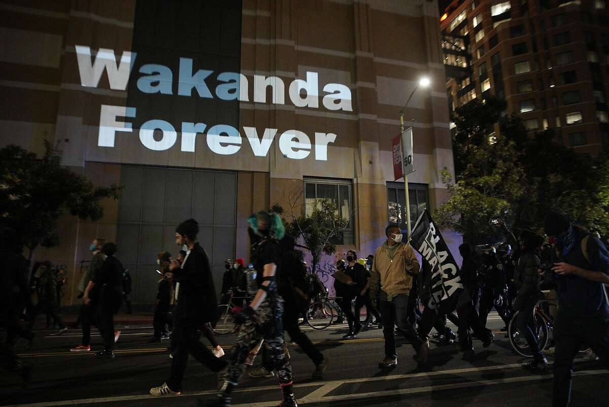 Wakanda Forever is projected onto the building during a Black Lives Matter march, Friday, Aug. 28, 2020, in Oakland, Calif. People demanded justice for Jacob Blake, who survived being shot in the back by police officers in Kenosha, Wisconsin.
