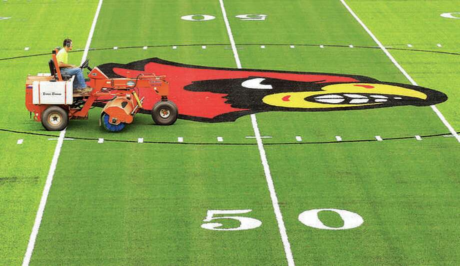 A worker drives across the face of the Redbird in the center of Alton's new artificial turf football field at Public School Stadium on State Street. The new football field is essentially complete, but won't be used for prep football until next spring. The IHSA moved football from fall to spring because of the coronavirus pandemic. Photo: John Badman | The Telegraph