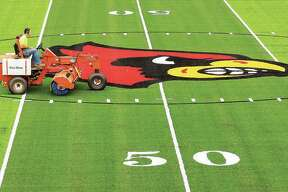 A worker drives across the face of the Redbird in the center of Alton's new artificial turf football field at Public School Stadium on State Street. The new football field is essentially complete, but won't be used for prep football until next spring. The IHSA moved football from fall to spring because of the coronavirus pandemic.