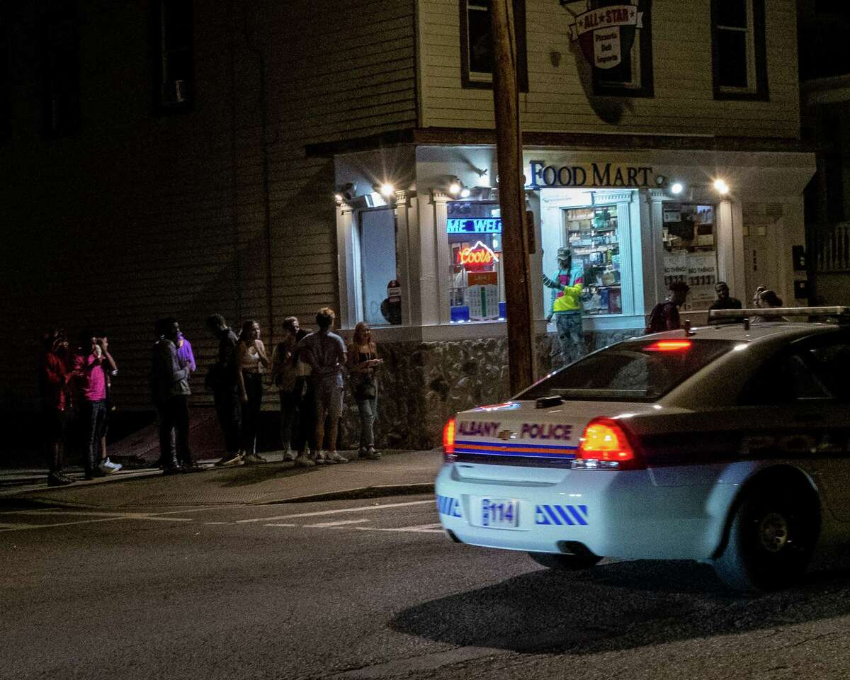 An Albany police car cruises by a crowd of UAlbany students who gathered outside the Food Mart at the corner of Quail Street and Hudson Avenue in Albany, NY, on Friday, Aug. 28, 2020 (Jim Franco/special to the Times Union.)