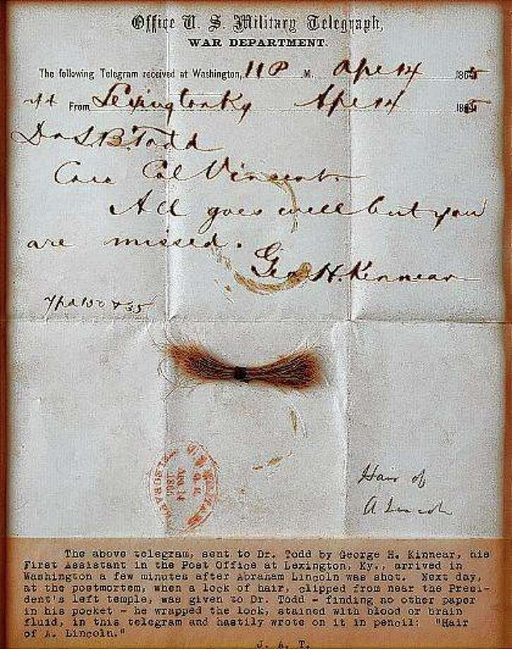 A bloodstained telegram and lock of hair from President Abraham Lincoln is to be auctioned Sept. 12 by Boston-based auction firm RR Auction. The lock of hair was removed during Lincoln's postmortem examination in April 1865 after he was fatally shot by John Wilkes Booth at Ford's Theatre in Washington. Photo: Nikki Brickett | RR Auction Via AP