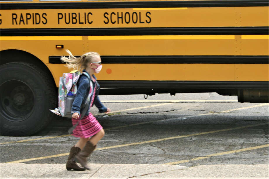 Day one of the 2020-2021 school year is complete as students are dismissed from Riverview Elementary School in Big Rapids. Students emerged from the building one by one to maintain social distancing, wearing face coverings, as they found their way to their buses or their waiting parents. Photo: Pioneer Photo/Cathie Crew