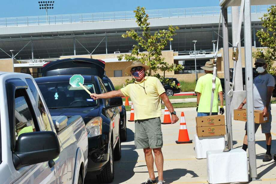 A volunteer directs traffic at Planet Ford Stadium in Spring at the Super Food Site distribution recently for families needing food assistance. Photo: Submitted
