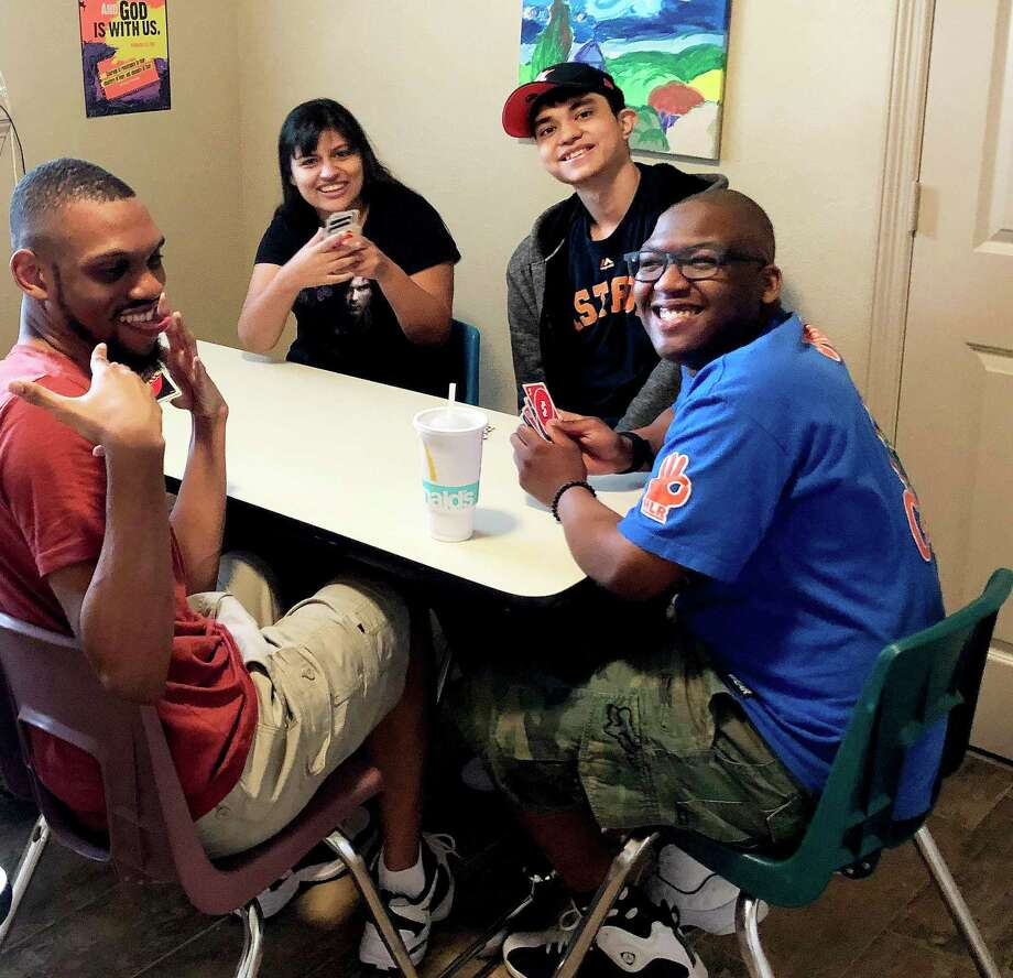In this photo taken before the pandemic, Julian, far right, and his friends enjoy a fun game of cards. The Cy-Fair graduate is happy to be in a program that fits his and his friends. Photo: Submitted