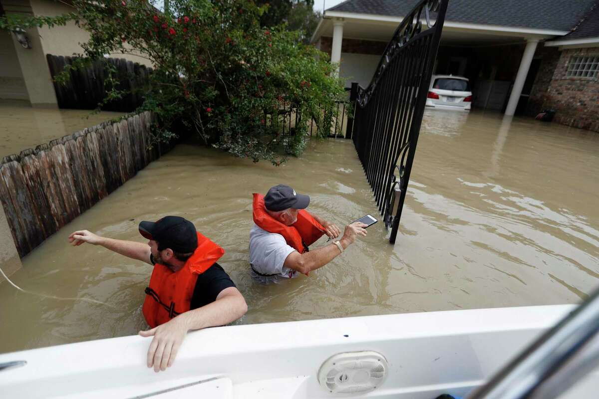 Chris Pitts, left, helps his father-in-law, Mike Stamps, out of a boat in floodwater at his home in the Kingwood Greens Subdivision from the San Jacinto River due to Tropical Storm Harvey, Wednesday, Aug. 30, 2017, in Kingwood. Stamps was there to retrieve his two cats, who had to be left behind, as he was evacuated on a jet ski Tuesday. ( Karen Warren / Houston Chronicle )