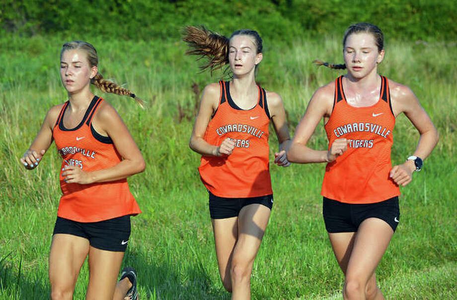 Edwardsville's Makenna Lueking, left, Maya Lueking, middle, and Riley Knoyle run during the first mile of Saturday's season-opening dual meet against East St. Louis at Frank Holten State Park. Photo: Scott Marion/The Intelligencer