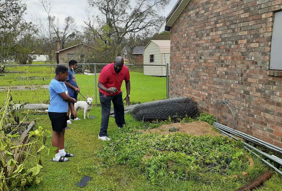 David Miller salvages a tiny watermelon from his flattened garden behind his house in Lake Charles. Sons, William (left) and David III, along with their fog, Bill, survey the damage. Photo: Jenny Deam, Houston Chronicle / Staff / © 2020 Houston Chronicle