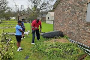 David Miller salvages a tiny watermelon from his flattened garden behind his house in Lake Charles. Sons, William (left) and David III, along with their fog, Bill, survey the damage.