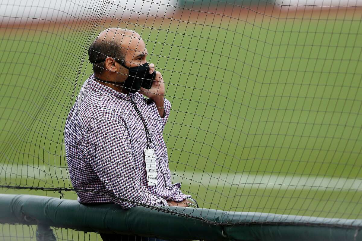 President of Baseball Operations Farhan Zaidi of the San Francisco Giants talks on the phone before the postponement of the game against the Los Angeles Dodgers at Oracle Park on August 26, 2020 in San Francisco, California.