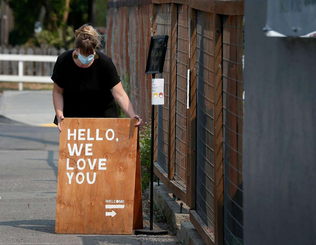 Boon restaurant general manager Mags van der Veen arranges a sign to attract diners after reopening in Guerneville, Calif. on Saturday, Aug. 29, 2020. The town on the Russian River is gradually reopening after evacuation orders were lifted from the LNU Lightning Complex fires.
