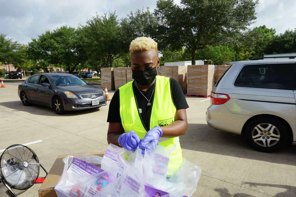 Raven Barbarin prepares to deliver personal protective equipment to vehicles lining up at a Fort Bend County distribution event outside Cinco Ranch Branch Library on Friday, Aug. 28.