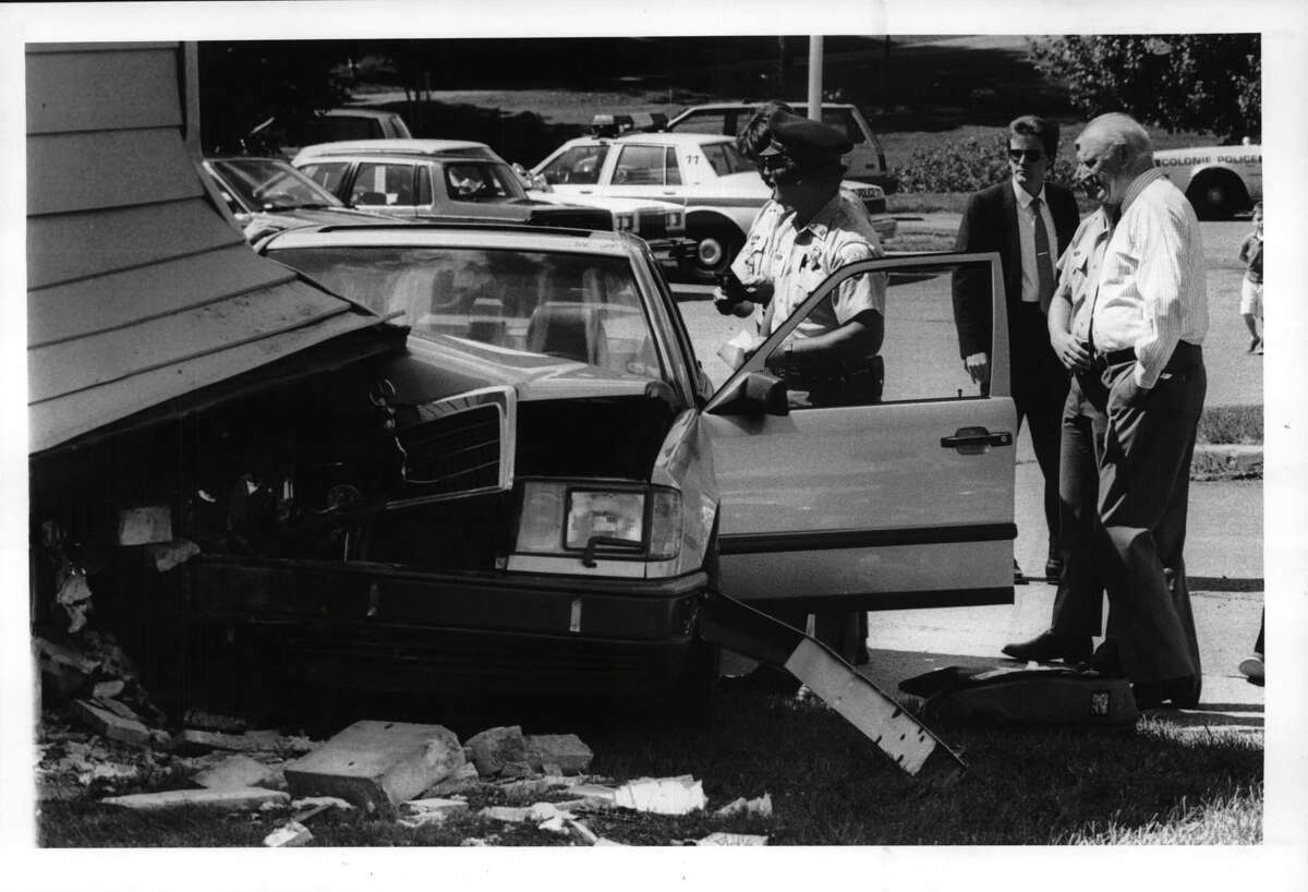 Colonie Police Department, New York - Chief James Flater Undated (far right) checks the damage to the building where his office is and to the late model Mercedes that hit the building this morning. August 30, 1990 (Skip Dickstein/Times Union Archive)