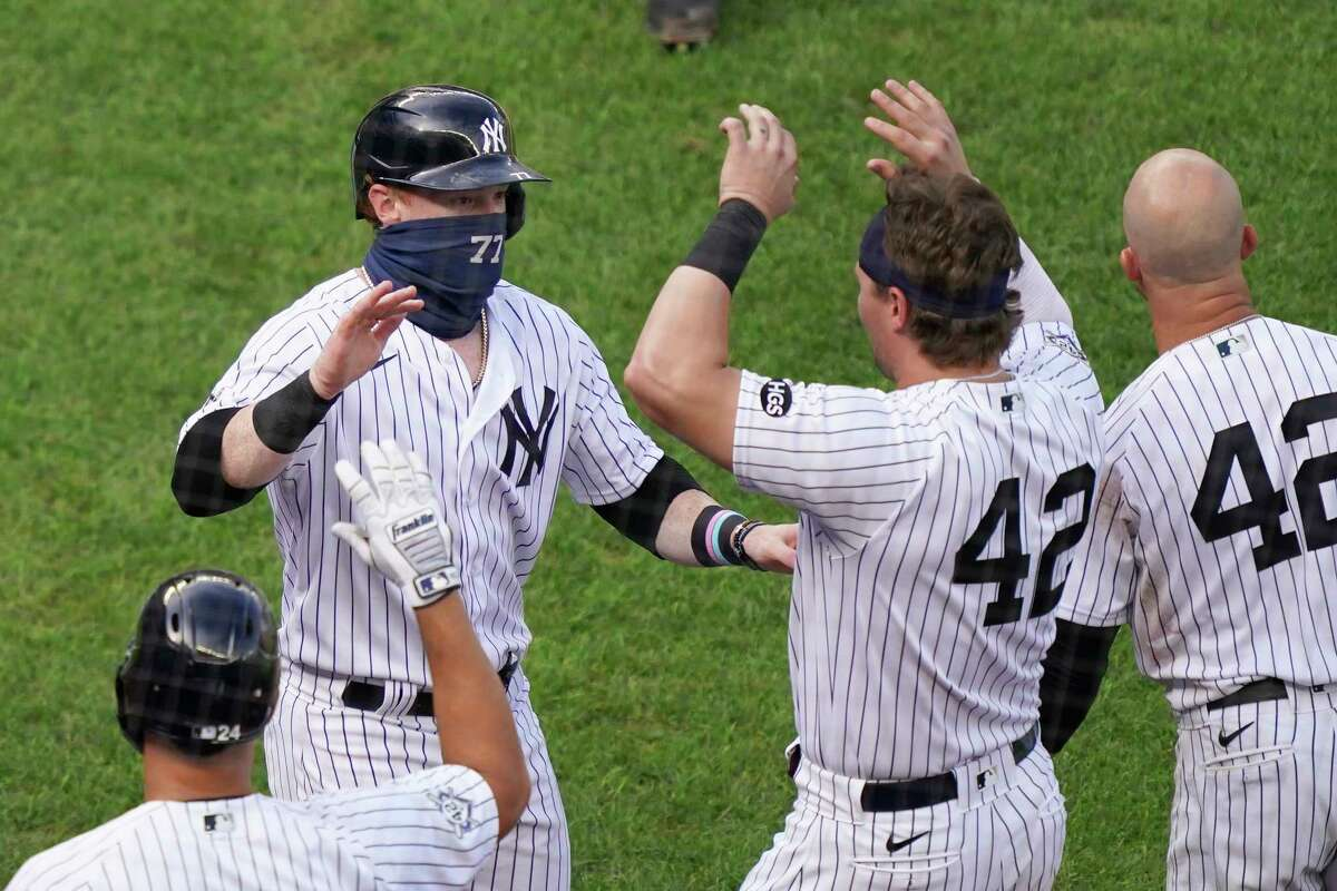 New York Yankees' Clint Frazier (77) celebrates with teammates after scoring the game-winning run on a wild pitch by New York Mets relief pitcher Dellin Betances in the ninth inning of a baseball game, Saturday, Aug. 29, 2020, in New York. The Yankees won 2-1. (AP Photo/John Minchillo)