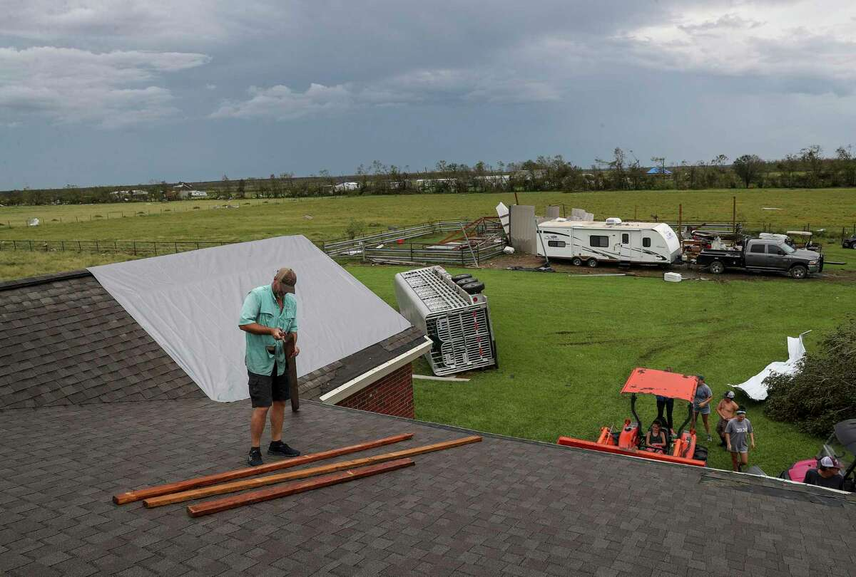 Jason Leonards helps nail a tarp on the roof of his brother's home Friday, Aug. 28, 2020, in Holmwood. The home was damaged when Hurricane Laura made landfall in the area Thursday morning.