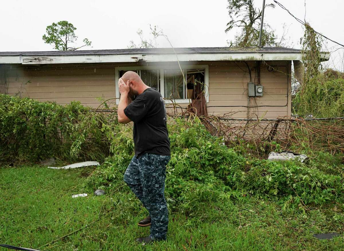 Jared Johnson covers his face after checking up on a friend's home, during the aftermath of Hurricane Laura, Friday, Aug. 28, 2020, in Lake Charles, La.