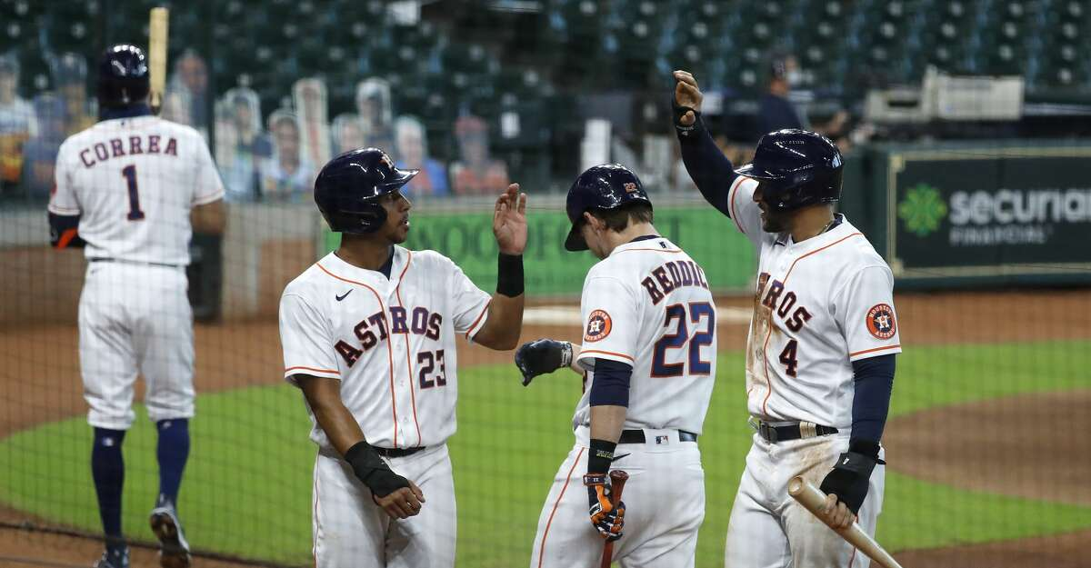Houston Astros Michael Brantley (23), George Springer (4) and Josh Reddick (22) celebrate after Kyle Tucker's three-run triple during the first inning of game two of a double header during an MLB baseball game at Minute Maid Park, Saturday, August 29, 2020, in Houston.