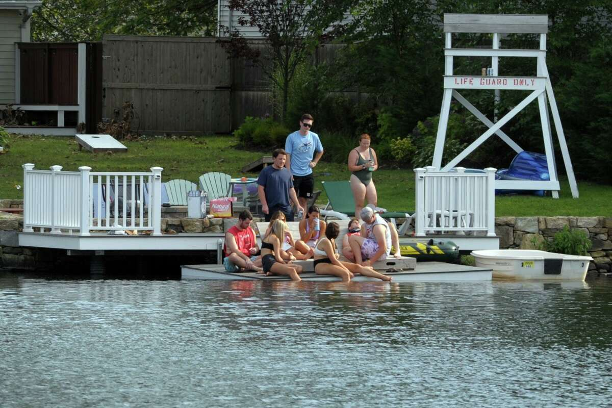 Ten people socialize on a dock behind a home on Lake Forest, in the Lake Forest neighborhood of Bridgeport, Conn. Aug. 28, 2020.