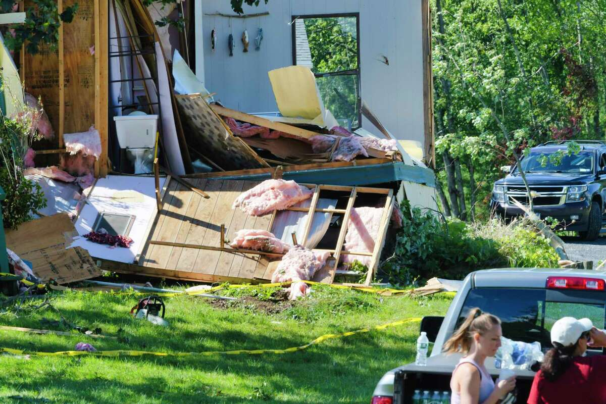 People clean up damage from a storm at a home on McDermott Road on Sunday, Aug. 30, 2020, in Stillwater, N.Y.